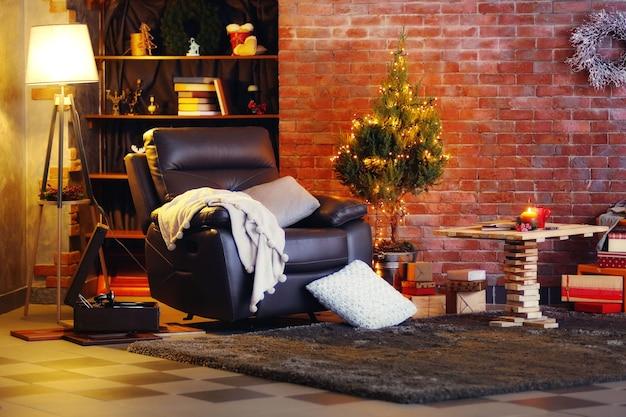 小さなモミの木、アームチェア、ランプのあるクリスマスの装飾が施された部屋