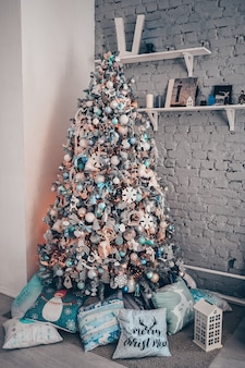Christmas decorated tree in blue colors with different pillows on a floor