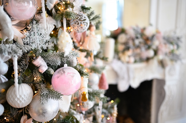 Christmas decorated tree in soft pink colors against the background of white classic fireplace with christmas decorations.