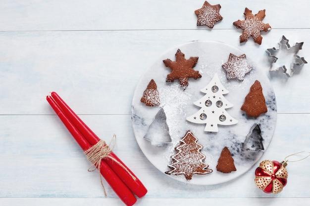 2つの赤いろうそくと砂糖の粉を振りかけたクリスマスの装飾とクッキー