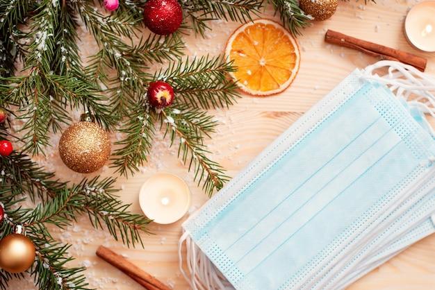 Рождественские украшения и медицинские маски на деревянном столе.