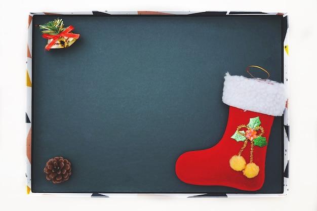 Рождественские украшения и ботинок красного санты на доске. плоская планировка