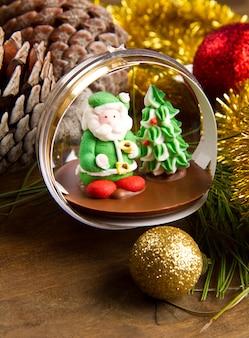 Новогоднее украшение и шоколад санта-клауса на деревянный стол