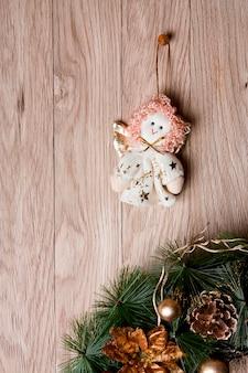 Новогоднее украшение - ангел и венок, свисающие на деревянном фоне