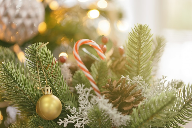Christmas decoration background with pine leaves, pine cones, holly balls, candy cane and bauble.