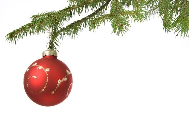 白い背景の上のクリスマスの装飾ボールとモミの枝