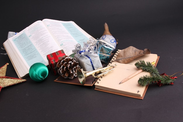 Christmas decoration and the bible with black backdrop.
