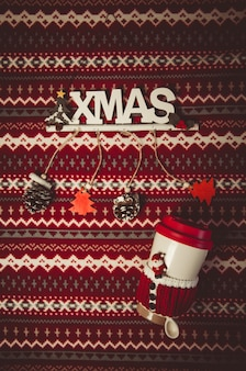 Christmas decoration and bottle with santa spoon on red and white pattern