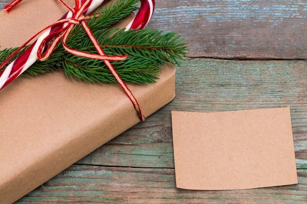 크리스마스 장식. 스티커 메모와 함께 크리스마스 선물 상자입니다. 아름다운 포장. 나무 바탕에 빈티지 선물 상자입니다. 수공.