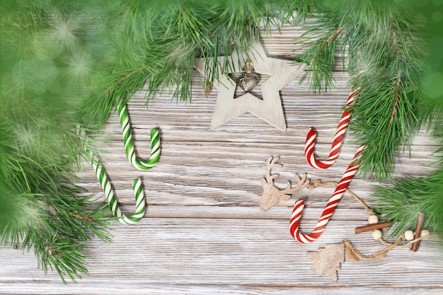 Christmas decoration on branches of christmas tree. candy canes and wooden toys on wood background with light and bokeh.