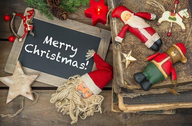 クリスマスの飾りキャンドルとヴィンテージのおもちゃ。サンプルテキスト付き黒板メリークリスマス!レトロなスタイルのトーンの写真。ダークデザインのセレクティブフォーカス