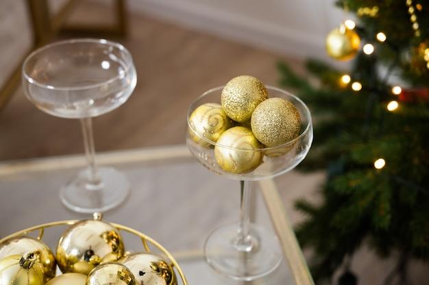 クリスマスの飾り、シャンパングラス、金色のクリスマスつまらないもの。クリスマスツリーと新年のインテリア。