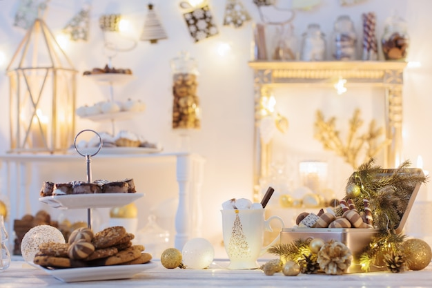 Christmas decoration cocoa bar with cookies and sweets in white and gold and vintage style
