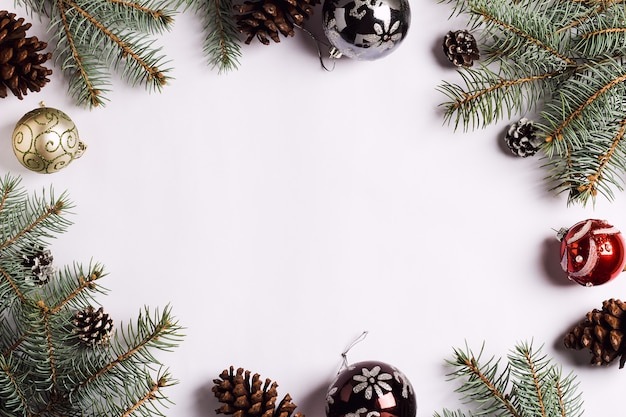 Christmas decoration composition pine cones balls spruce branches on white festive table