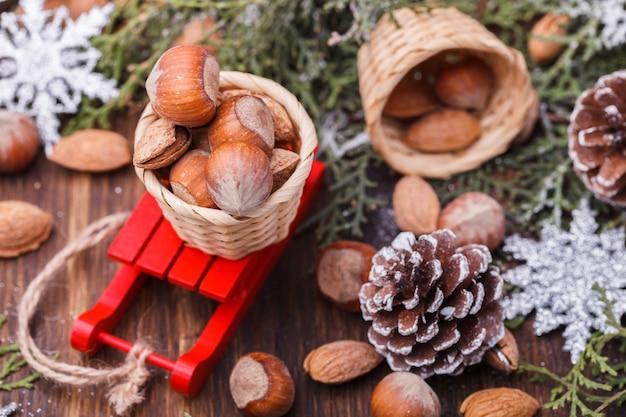 Рождественские украшения. шишки, миндаль и фундук на санках.