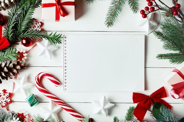 クリスマスの飾り。紙のカードノートとクリスマスツリーの枝で作られた創造的なレイアウト。
