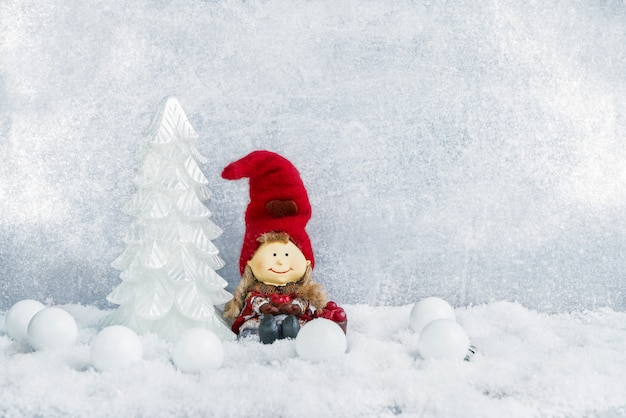 Christmas decoration. decorative christmas fir tree and gnome in snow. copyspace