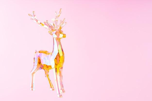 ピンクの背景にクリスマスの装飾鹿の置物。ホログラフィックおもちゃの鹿とクリスマスの作曲。お祝いの休日のコンセプト。コピースペース