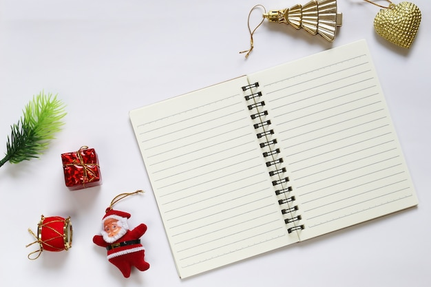 Christmas decoration and empty notebook on white background.