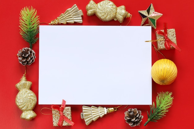 Christmas decoration and empty paper note on red background.