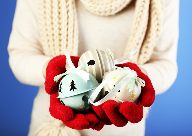 Christmas decoration in female hands on color surface
