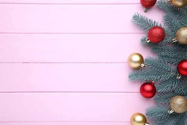 Christmas decoration. fir-tree branch with balls, bows on a pink background
