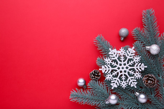 Christmas decoration. fir-tree branch with balls, bumps, snowflake on a red background