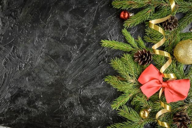 クリスマスの飾り。ボール、ギフト、松ぼっくり、黒い木の表面に弓とモミの木の枝