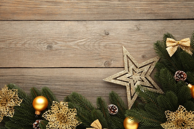 Christmas decoration. fir-tree branch with gold balls, christmas flower and star on grey