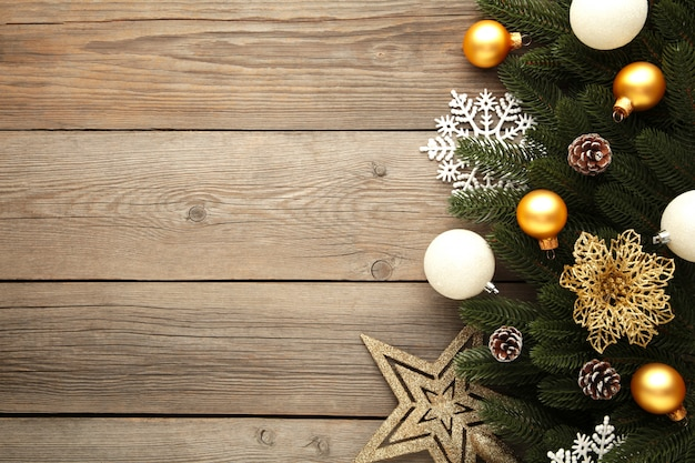 Christmas decoration. fir-tree branch with gold and silver balls, christmas flower and star on grey