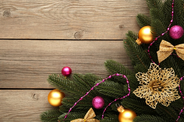 Christmas decoration. fir-tree branch with pink and gold balls on grey background
