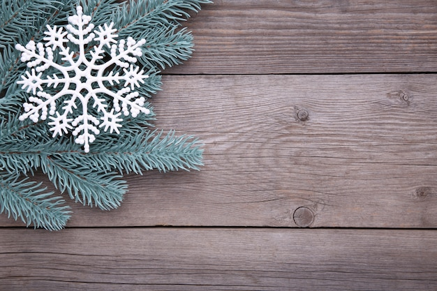 Christmas decoration. fir-tree branch with snowflake on a grey background