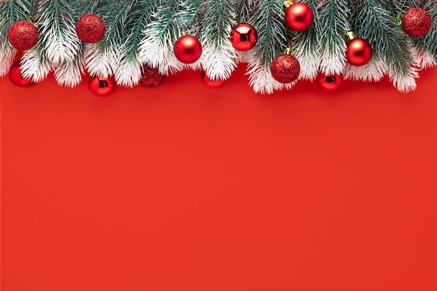 Новогоднее украшение еловые ветки со снегом, красные шары на красной композиции Premium Фотографии
