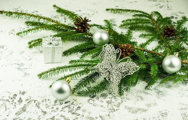 휴일을 위한 크리스마스 장식입니다. 은색 공이 있는 녹색 가문비나무 가지와 눈 덮인 배경에 반짝이는 나비. 가까운 각도.