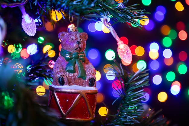 Christmas decoration in the form of a bear on a drum hanging on a christmas tree in the background many garlands in different colors glow.