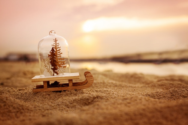 Christmas decoration in the form of a glass ball with a christmas tree and a snowman on the beach