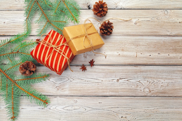 Christmas decoration, gift box and pine tree branches on wood
