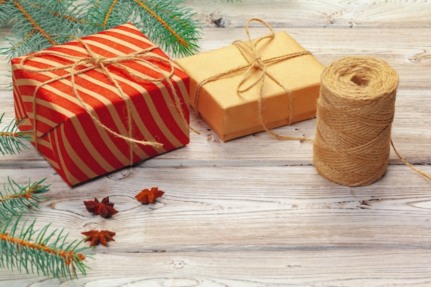 Christmas decoration, gift box and pine tree branches on wooden background