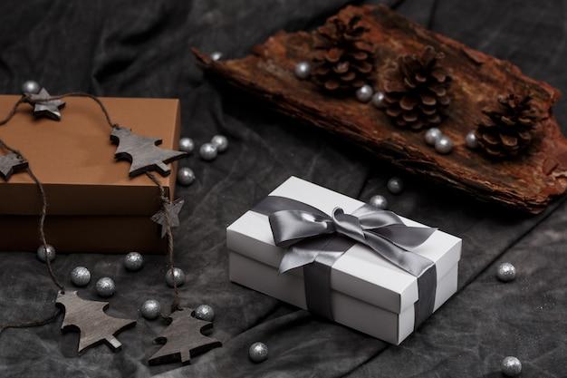 Decorazioni natalizie e scatole regalo su sfondo grigio.