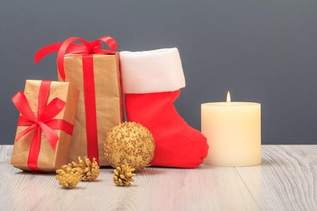 クリスマスの飾り。ギフトボックス、サンタのブーツ、おもちゃのボール、コーン、灰色の背景に燃えるろうそく。クリスマスのグリーティングカードのコンセプト。