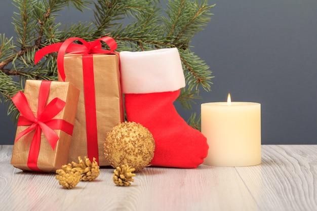 クリスマスの飾り。ギフトボックス、サンタのブーツ、おもちゃのボール、コーン、燃えるろうそく、灰色の背景に天然のモミの木の枝。クリスマスのグリーティングカードのコンセプト。