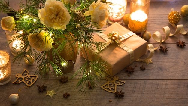 Christmas decoration. gift, candles, lights, golden balls on a wooden rustic table. xmas composition of pine branches and english roses in a vase. golden and brownish aesthetics.