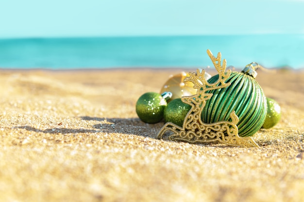 Christmas decoration green balls and gold reindeer on the tropical beach near ocean