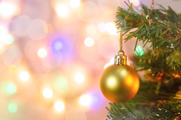 クリスマスの飾り。松の枝に金のボールをぶら下げクリスマスツリーの花輪と装飾品をコピースペースで抽象的なボケ味の背景の上に