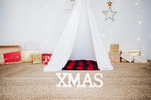 Christmas decoration at home, lights, teepee and presents. christmas time