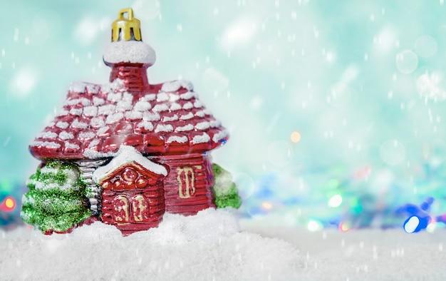 雪が降ると焦点がぼけた青い背景に雪の中に立っているクリスマスの装飾家