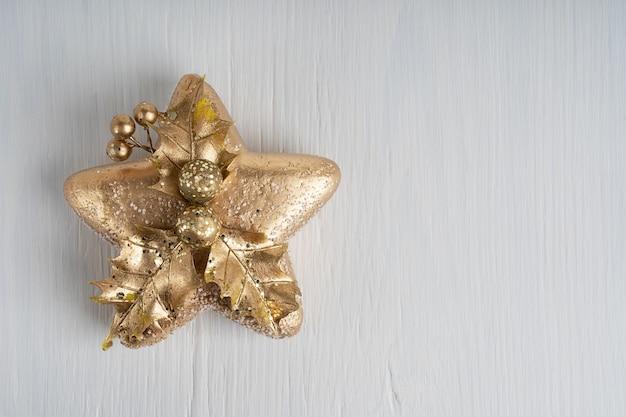 Новогоднее украшение в форме золотой звезды на белом деревянном фоне