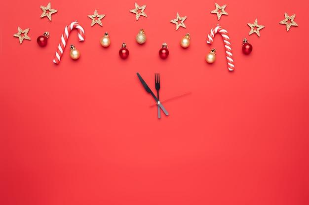 赤い背景の時計の形でクリスマスの装飾