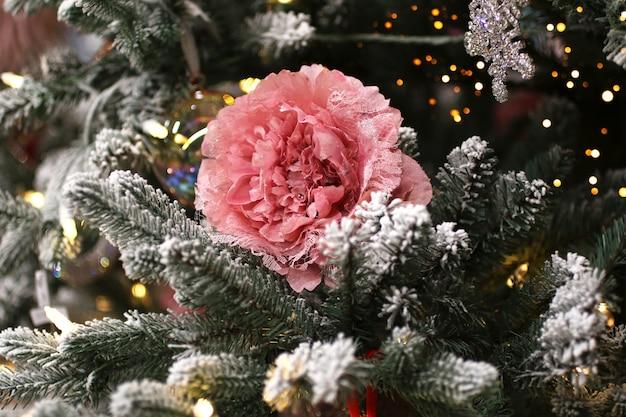 トウヒの枝にあるバラの形をしたクリスマスの飾り。ショップの装飾。