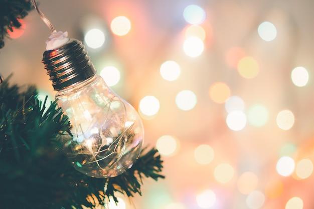 크리스마스 장식. 소나무 가지에 매달려 있는 전구 크리스마스 트리 화환 및 복사 공간이 있는 추상 보케 배경 위에 장식품